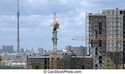 Cranes operate above apartment building construction site in front of Ostankino Tower