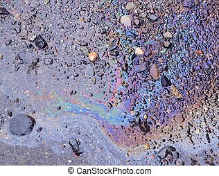 Spilled oil on wet ground - Oily sheen from spilled oil on...