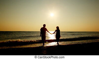 Girl and boy go holding hands from sea, silhouettes on sunset, part2