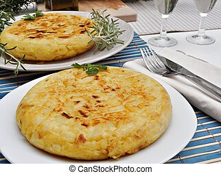 Two Spanish omelet of potatoes decorated with branches of...