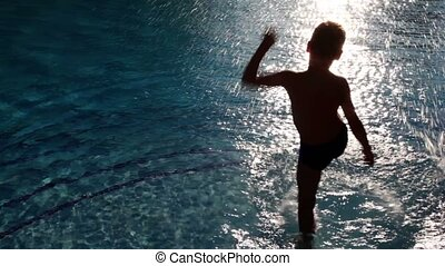 Boy stand in pool and splutter water by leg making spatters...