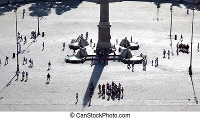 Base of the Flaminio obelisk in the square, people sitting...