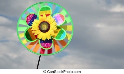 Toy with sunflower in center, that spins on the background of sky