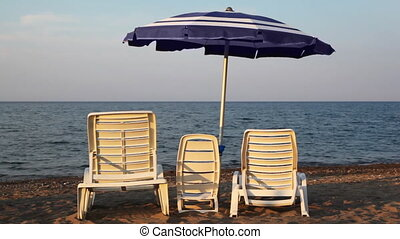 Chairs in three sizes are at seashore under umbrella - White...