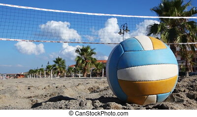 Ball lies on sand under volleyball net at beach near palm...