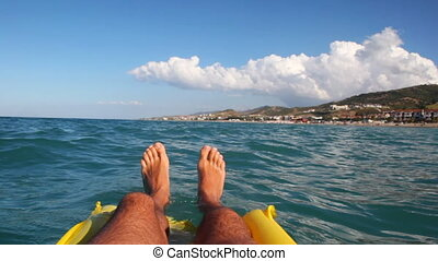 Legs of man swim on sea surface with mattress - legs of man...