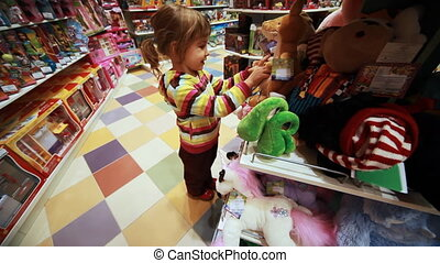 little girl carefully choose toy in shop