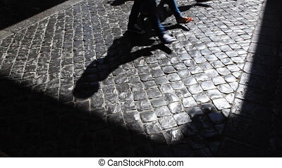Legs and shadows of pilgrims in church move along pavement