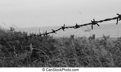 Barbed wire by the beach. - Closeup of barbed wire with...