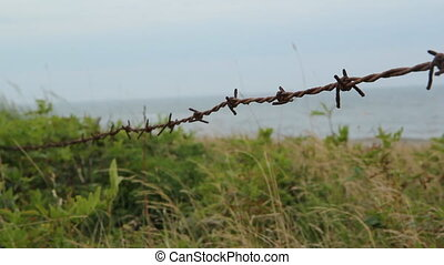 Barbed wire by the beach. - Closeup of rusty barbed wire...