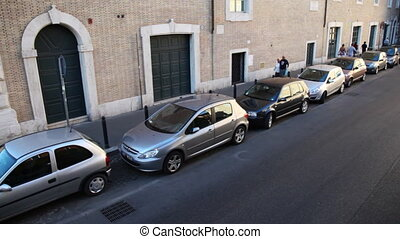 Cars are at curb, people walk streets of city - ROME -...