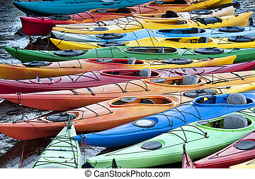 Kayaks - Colorful fiberglass kayaks tethered to a dock as...