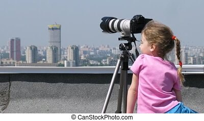 Little girl on top of the roof play with digital camera,...