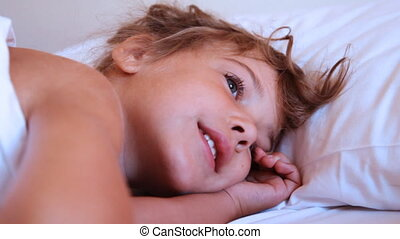 Someone trying to wake up cute little girl on pillow
