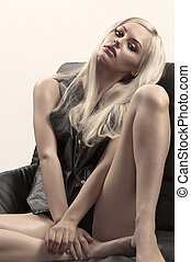 blonde girl sitting on a chair - glamour shot of a sexy...