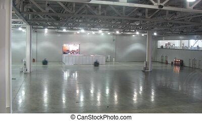 Washing machines cleanup floor inside expo center, time...