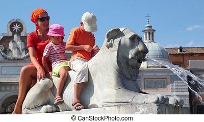 Mother and her kids sit on statue of lion near Flaminio obelisk