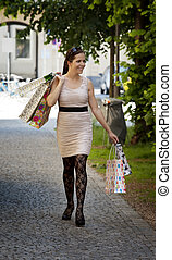 Woman with shopping bags while shopping - A young woman...