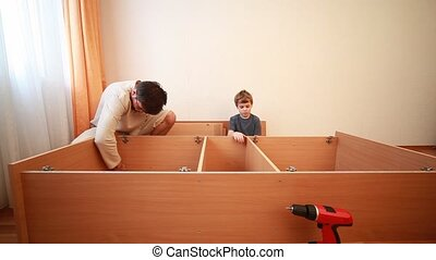 Father and son construct wooden cabinet at home - Father and...