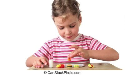 Girl puts on tray artificial food one by one, which are...