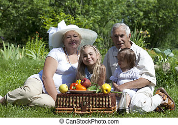 Picnic - Mature couple with two granddaughters picnicked on...