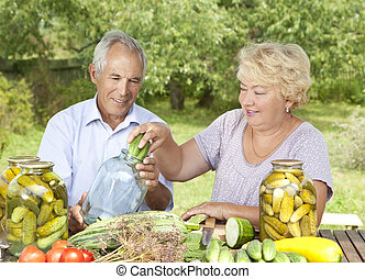 Happy elderly couple making home made pickles
