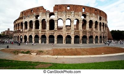 Area near Coliseum and its exterior, people walk around at...