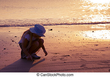 Little girl on the seashore in sunset