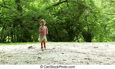 Girl runs closer across forest meadow all strewn fluff, at...