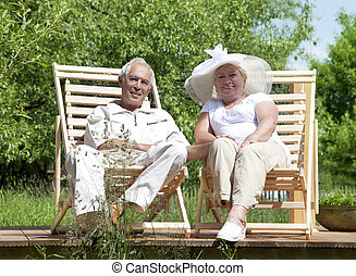 Senior loving couple have a rest in a deckchair