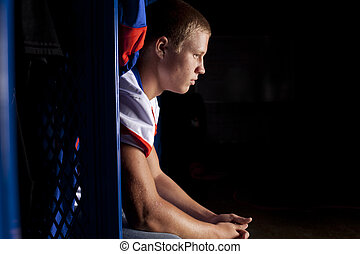 Defeated - A football player sits in his locker thinking...