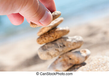Stones on sand with hand.