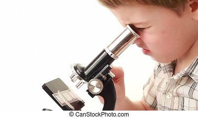 Little boy works with microscope, closeup, side view