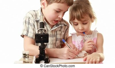 Brother sitting near microscope teach his little sister