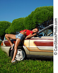 Pretty woman pin-up style lay on retro car
