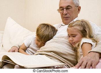 Grandpa with his grandchildren - Grandpa is reading book to...