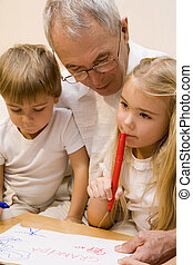 Grandpa with his grandchildren - Grandpa is teaching his...