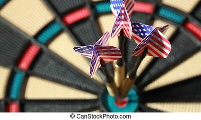 Three darts with American flag hit bullseye on dartboard,...