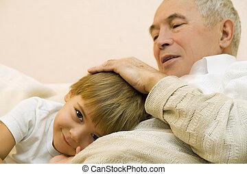 senior with his grandchild - Grandpa stroke the head of his...