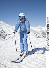 Alpine skiing - Young woman with ski against mountains