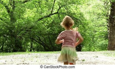 Girl runs away across forest meadow all strewn fluff