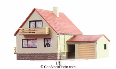 Little toy house turning around on transparent platform,...