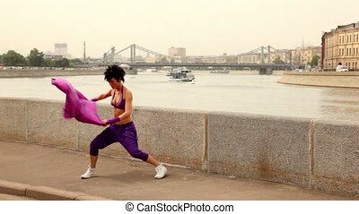 Flexible girl actively dances with cloth on quay, two ships...