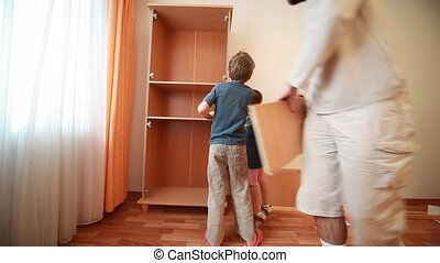 Father and kids construct wooden closet at home - Father and...