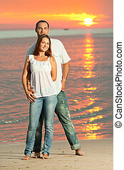 Couple - Young couple near the sea at sunrise