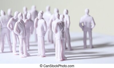 Group of little unpainted toy humans stand and drop shadows,