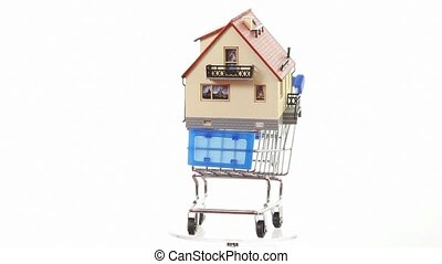 House model placed on shopping cart turning around on platform
