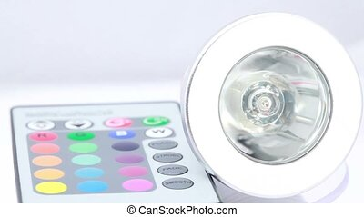 Lamp and remote control lies near, composition rotates