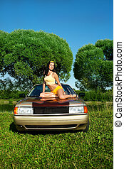 Sexy young woman sit on retro car