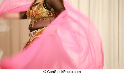 Belly dancer in black dress perform on stage, closeup view